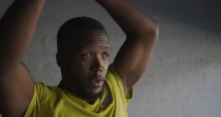 head over : Front view close up of an athletic African American man in sportswear standing against a wall stretching his arms over and behind his head while training in the city, slow motion