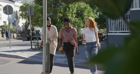 socialising : Front view of a young Caucasian woman, a young African American woman and a young mixed race woman wearing a hijab walking and talking together in a sunny city street holding takeaway coffees, trees behind them, slow motion