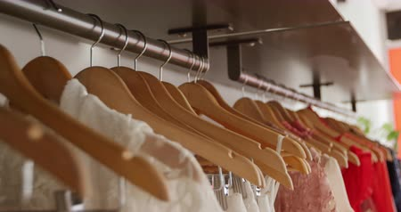 sem camisa : Close up of a line of dresses on clothes hangers displayed hanging on rails in a womens clothing shop, slow motion Stock Footage