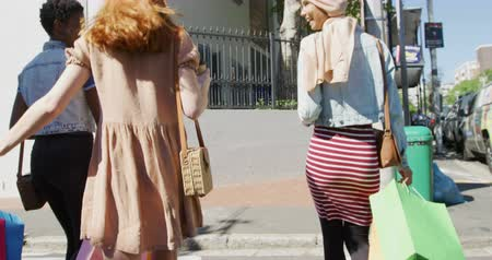 provést : Rear view of a young Caucasian woman, a young African American woman and a young mixed race woman wearing a hijab walking and talking together in a sunny city street carrying shopping bags and handbags, slow motion