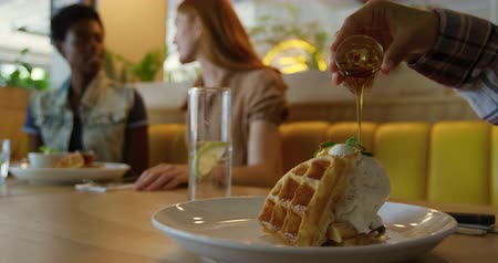 pour out : Side view mid section of a young mixed race woman sitting with girlfriends in a coffee shop, pouring syrup on a plate of waffles and ice cream, slow motion
