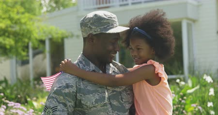 saludo militar : Side view close up of a young adult African American male soldier in the garden outside his home, holding and embracing his young daughter, who is holding a US flag, they are looking at each other smiling, slow motion Archivo de Video