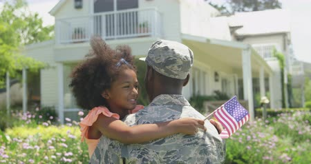 saludo militar : Rear view close up of a young adult African American male soldier in the garden outside his home, holding and embracing his young daughter, who is facing the camera, smiling with eyes closed and holding a US flag, slow motion