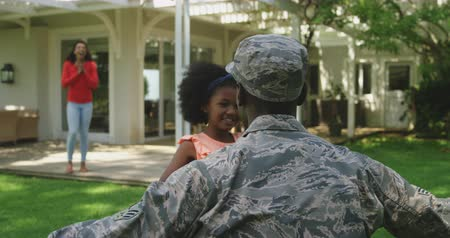ajoelhado : Rear view close up of a young adult African American male soldier kneeling in the garden outside his house while his young daughter runs to greet him and his mixed race wife walks behind her, slow motion