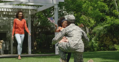 saludo militar : Rear view of a young adult African American male soldier kneeling in the garden while his young daughter runs to greet him and his mixed race wife walks behind her, slow motion