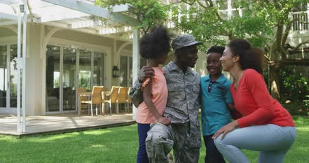 saludo militar : Front view of a young adult African American male soldier in the garden outside his home, kneeling with his arms around his young son and daughter, his mixed race wife beside them, all smiling at each other, slow motion