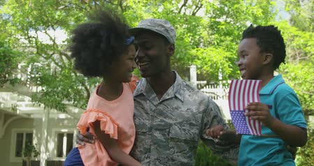 saludo militar : Front view of a young adult African American male soldier in the garden outside his home, kneeling with his arms around his young son and daughter, his son is holding a US flag, slow motion