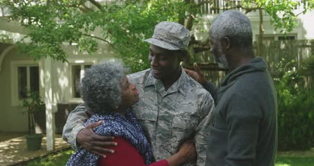homecoming : Front view close up of a happy young adult African American male soldier embracing with his parents, all of them smiling, in the garden outside their house, slow motion Stock Footage