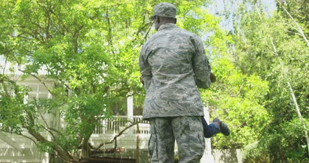 saludo militar : Front view of a young adult African American male soldier in the garden outside his home, holding his young son and swinging him around, both smiling, their house in the background, slow motion Archivo de Video