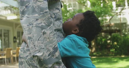 saludo militar : SIde view mid section of a young adult African American male soldier in the garden outside his home, embracing his young son, who is looking up at him smiling and holding a US flag, thier house in the background, slow motion