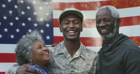 去る : Portrait of a young adult African American male soldier embracing with his parents, all of them smiling to camera in front of a US flag, slow motion