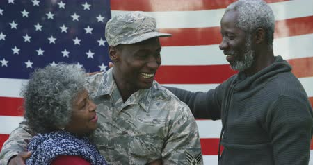 katonai : Front view close up of a happy young adult African American male soldier embracing with his parents, all of them smiling, in front of a US flag, slow motion