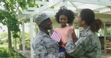 homecoming : Front view of a young adult African American male soldier and a young mixed race female soldier in the garden outside their home, talking and embracing with their young daughter, who is smiling and holding a US flag, slow motion Stock Footage