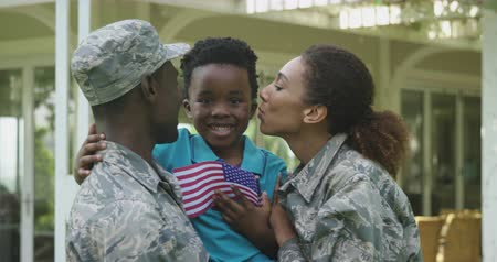 homecoming : Front view of a young adult African American male soldier and a young mixed race female soldier in the garden outside their home, kissing and embracing their young son, who is smiling and holding a US flag, slow motion Stock Footage