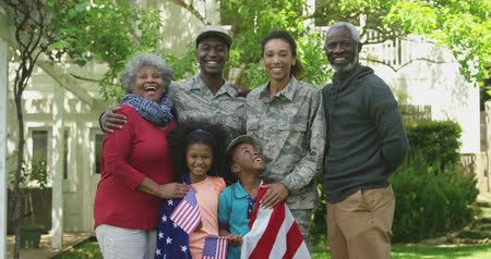 vader en zoon : Portrait of a young adult African American male soldier and a young adult mixed race female soldier with thier diverse multi-generation family in the garden outside their home, embracing and smiling to camera, a US flag draped over the shoulders of the ki