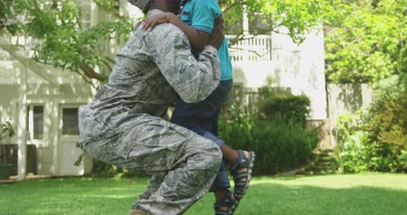 homecoming : Side view close up of a young adult African American male soldier kneeling in the garden outside his home, greeting his young son, picking him up, standing and embracing him, both smiling, their house in the background, slow motion Stock Footage