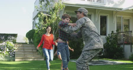 saludo militar : Rear view of a young adult mixed race male soldier in the garden outside his home, kneeling and picking up his young son, who runs to him holding a US flag, with his mother and sister holding hands and running behind him, slow motion