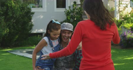 csatlakozott : Front view of a young adult mixed race male soldier in the garden outside his home, kneeling and embracing his young son and daughter, joined by his Caucasian wife for a family hug, slow motion