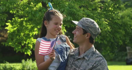 homecoming : Portrait close up of a young adult mixed race male soldier in the garden outside his home, carrying his daughter, who is waving a US flag, both smiling to camera, slow motion Stock Footage