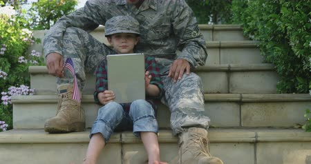 homecoming : Front view of a young adult mixed race male soldier in the garden outside his home, sitting on steps with his son, using a tablet computer and holding a US flag, the son wearing his army cap, slow motion Stock Footage