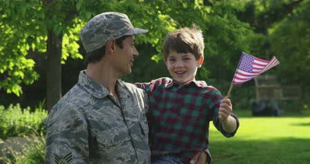 homecoming : Front view close up of a young adult mixed race male soldier in the garden outside his home, carrying his young son, who is waving a US flag, both looking at each other smiling, slow motion