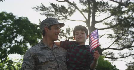homecoming : Front view of a young adult mixed race male soldier in the garden outside his home, carrying his son who is holding a US flag and looking at him smiling, backlit, slow motion
