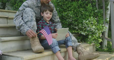 homecoming : Side view of a young adult mixed race male soldier in the garden outside his home, sitting on steps with his son, using a tablet computer and holding a US flag, both smiling, slow motion