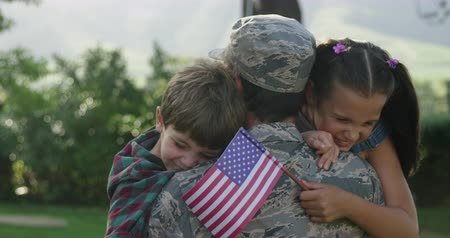 saludo militar : Rear view close up of a young adult mixed race male soldier in the garden outside his home, carrying his son and daughter, who are leaning over his shoulder smiling with eyes closed, the daughter holding a US flag, slow motion