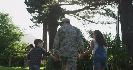 homecoming : Rear view of a young adult mixed race male soldier in the garden outside his home, holding hands and walking with his young son and daughter, his son holding a US flag, backlit, slow motion