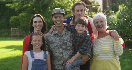 saludo militar : Portrait of a young adult mixed race male soldier and his diverse multi-generation family in the garden outside their home, embracing and smiling to camera, slow motion