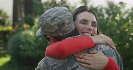 barre : Rear view of a young adult mixed race male soldier in the garden outside his home, embracing his young adult Caucasian female partner, who is smiling with eyes closed, slow motion Vidéos Libres De Droits