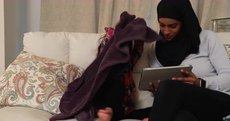 İslamiyet : Front view of a young mixed race mother wearing hijab with her young daughter in the sitting room, sitting on a sofa and using a tablet computer Stok Video