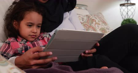 náklonnost : Front view close up of a young mixed race mother wearing hijab with her young daughter in the sitting room, sitting on a sofa and using a tablet computer Dostupné videozáznamy