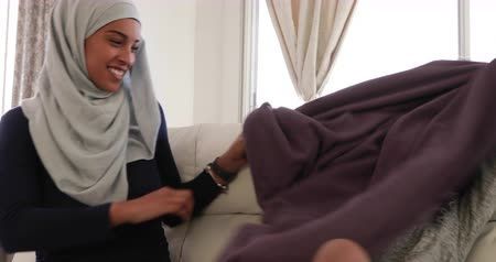 головной платок : Front view of a young mixed race mother wearing hijab with her young daughter in the sitting room, sitting on a sofa, playing together, the girl hiding under a blanket