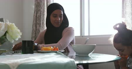 головной платок : Front view of a young mixed race mother wearing hijab with her young daughter in the kitchen, sitting at a table, the girl eating an orange, the woman using laptop computer