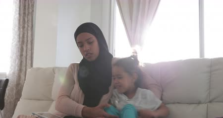 головной платок : Front view of a young mixed race mother wearing hijab with her young daughter in the sitting room, sitting on a sofa and using a tablet computer Стоковые видеозаписи