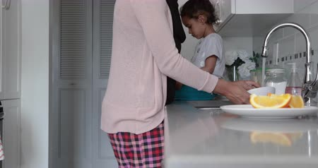 náklonnost : Side view of a young mixed race woman wearing hijab with her young daughter in the kitchen, the woman washing up, the girl sitting on worktop