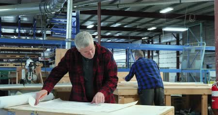 productiviteit : Front view of Caucasian male carpenter standing next to workbench checking plans with a young Caucasian male apprentice checking a piece of wood in woodshop