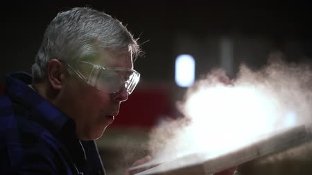 verimlilik : Side view close up of a Caucasian male carpenter wearing safety glasses, holding a piece of freshly cut piece of wood and blowing sawdust off in a woodshop, slow motion