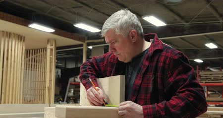 measure tape : Side view of a Caucasian male carpenter in woodshop wearing checked shirt, standing next to workbench, measuring a piece of wood Stock Footage