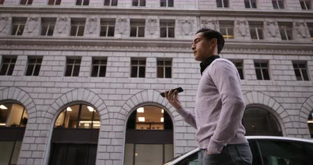 employed : Side view low angle of a young mixed race man talking on the smartphone walking in the city street with buildings in the background