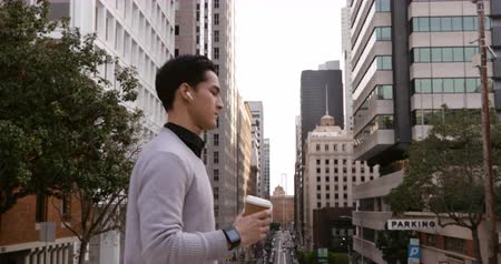 go away : Side view of a young mixed race man walking in the city street with earphones on, holding a takeaway coffee cup with buildings in the background