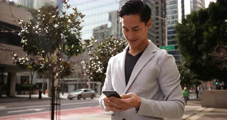 employed : Front view of a young mixed race man using a smartphone, standing in the city street with traffic and buildings behind hime