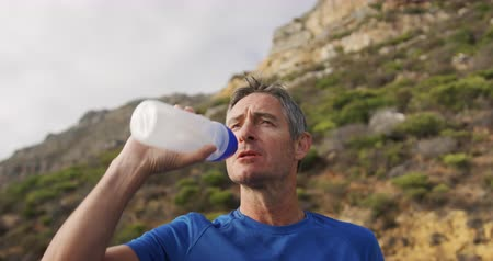 recovering : Front view close up of a Caucasian man running in the countryside by the coast taking a break and drinking from a water bottle