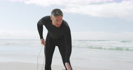 kayış : Front view of a caucasian father on a beach wearing a wetsuit and preparing his surfboard and leg rope before surfing, the sea in the background, slow motion Stok Video
