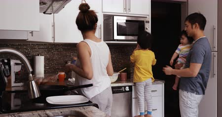 taburete : Side view of a Chinese Asian family busy in the kitchen together, the mother cooking using a frying pan on the hob, the father holding their young daughter in his arms and helping their son who stands on a stool to use the microwave oven
