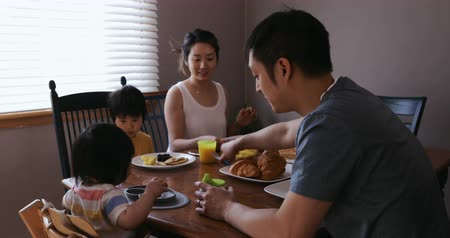 free throw : Side view of a Chinese Asian family in their dining room eating a meal together and talking, the young daughter sitting in a highchair throwing her cup and cutlery across the table