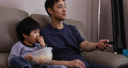 changer : Front view close up of a Chinese Asian man and his young son in their living room, sitting together on a sofa watching TV, the son eating popcorn from a bowl he is holding and the father using the TV remote control Stock Footage