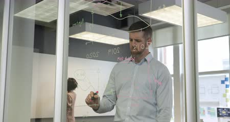 focussed : Front view of a Caucasian male business creative working in a modern office, drawing graphs and diagrams with a coloured pen on a glass wall, with two female colleagues visible working in the background. Seen through glass wall, with reflections Stock Footage