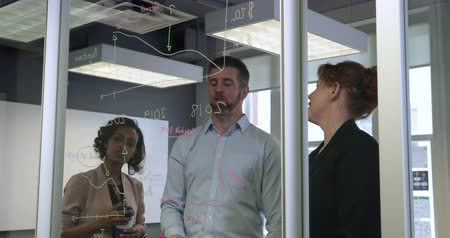 focussed : Front view of a mixed race businesswoman working with a Caucasian businessman and businesswoman in a modern office, standing and having a discussion, looking at graphs and diagrams drawn on a glass wall together. Seen through glass wall Stock Footage